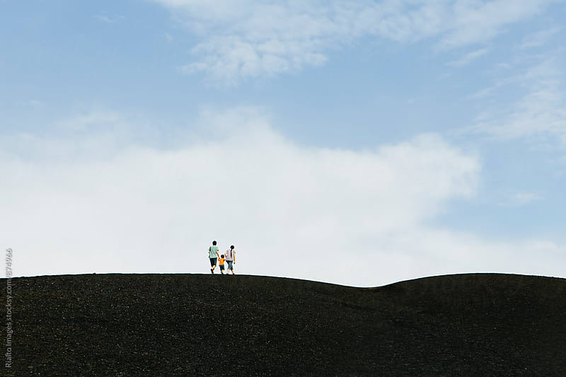 Family  in distance walking on volcanic hilltop by Paul Edmondson for Stocksy United