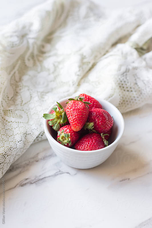 strawberries in a bowl with a lace cloth on a marble background by Gillian Vann for Stocksy United