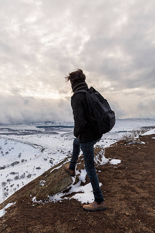 Man looking at winter landscape from the top of a mountain by Lior + Lone for Stocksy United