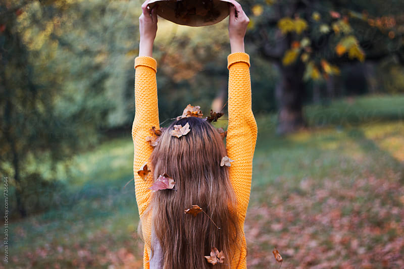 Autumn leaves falling from girl's hat by Jovana Rikalo for Stocksy United