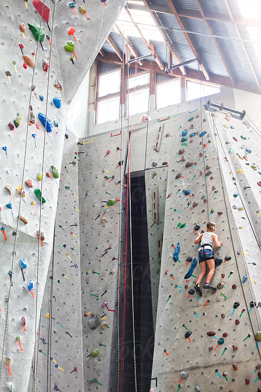Young girl climbing to the top of an indoor rock wall by Carolyn Lagattuta for Stocksy United
