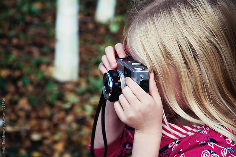 A little girl taking photographs with a vintage camera by Helen Rushbrook for Stocksy United