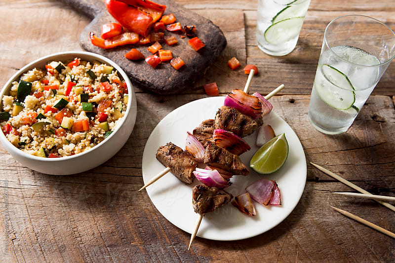 Grilled pork kebabs with garnish and beverages on wooden table by Trent Lanz for Stocksy United