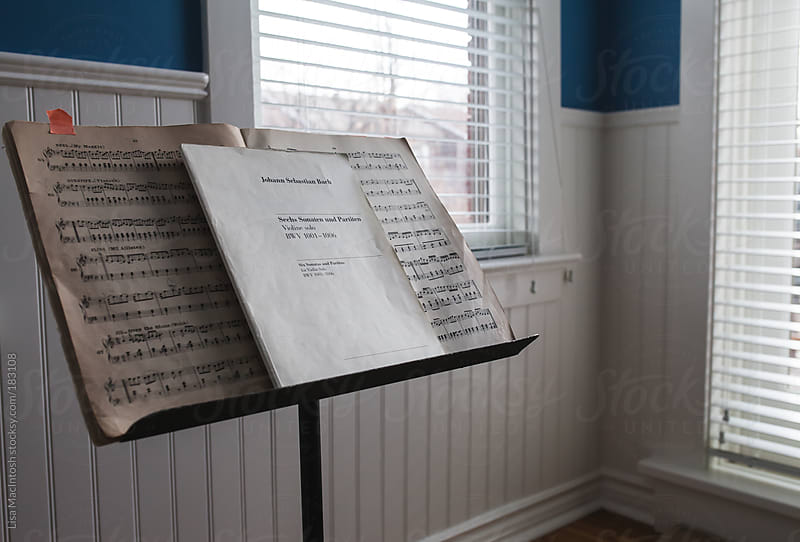 sheet music on stand in light filled room by Lisa MacIntosh for Stocksy United