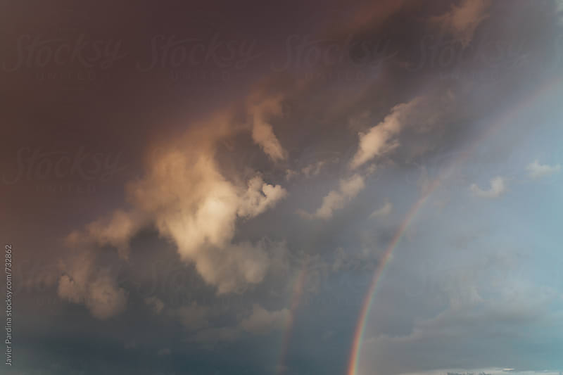 rainbow with storm clouds by Javier Pardina for Stocksy United