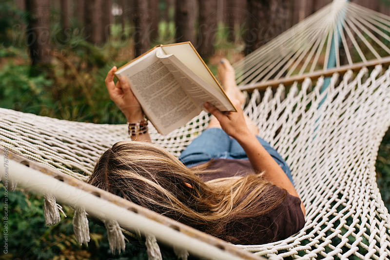 Female reading a book in a hammock by Gabriel (Gabi) Bucataru for Stocksy United