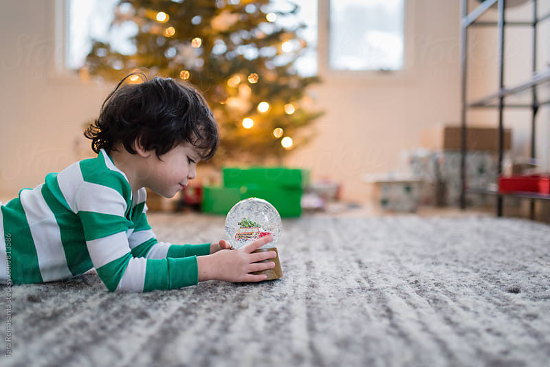young child with a snow globe in front of a Christmas tree by Tara Romasanta for Stocksy United