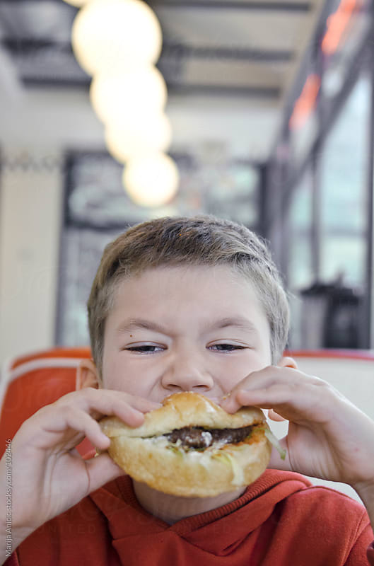boy eating a burger in a fast food restaurant by Marija Anicic for Stocksy United