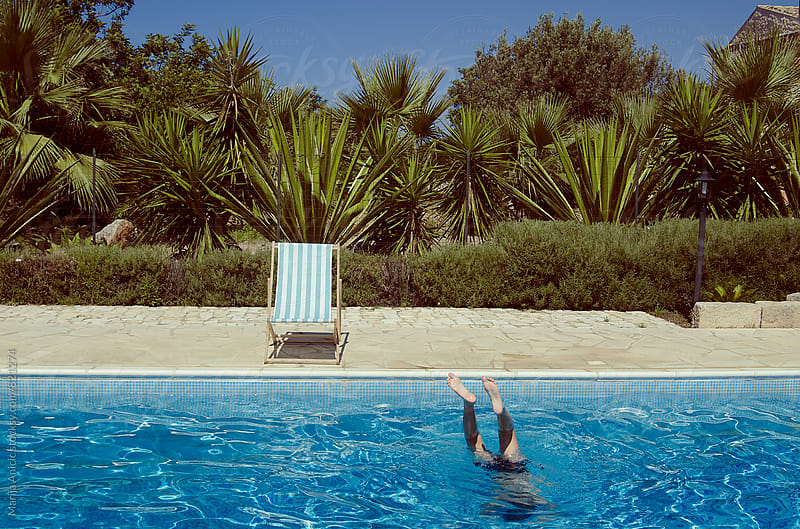 Boy enjoys swimming in the pool by Marija Anicic for Stocksy United