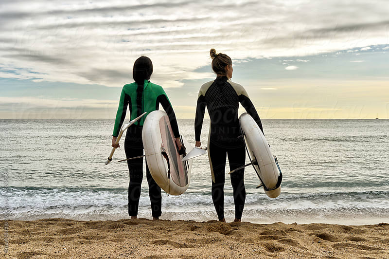 Two friends stand up with their paddle boards in Barcelona beach by Bisual Studio for Stocksy United