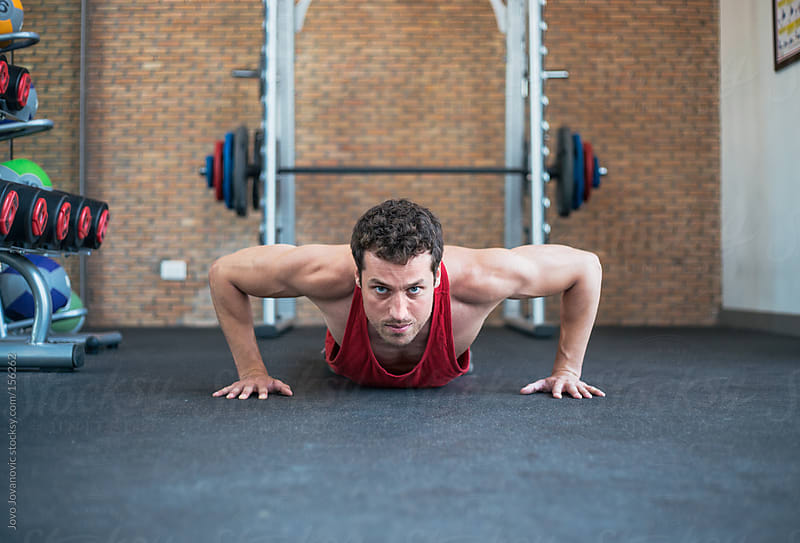 Young muscular man doing push ups by Jovo Jovanovic for Stocksy United