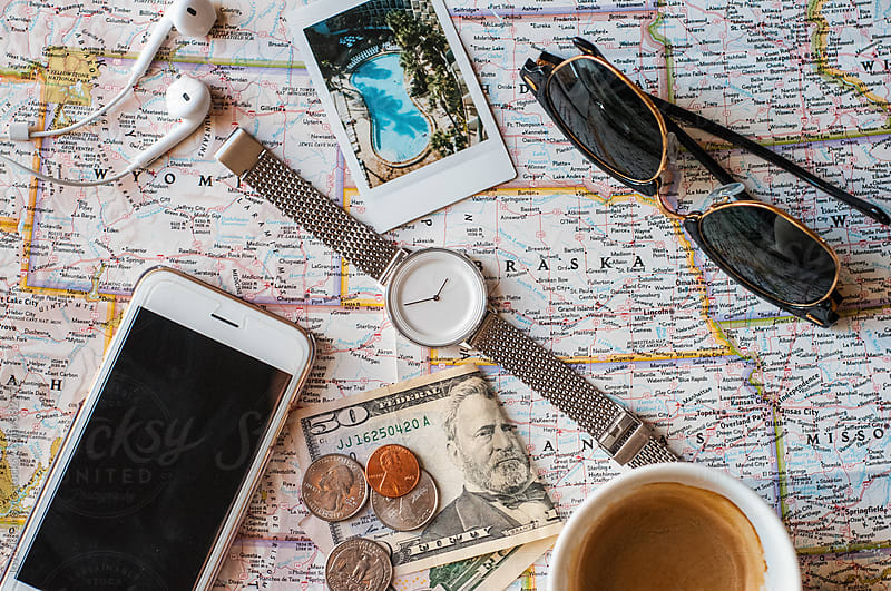 A smartphone, watch, sunglasses, money, coffee and a polaroid picture on a map  by Jovo Jovanovic for Stocksy United