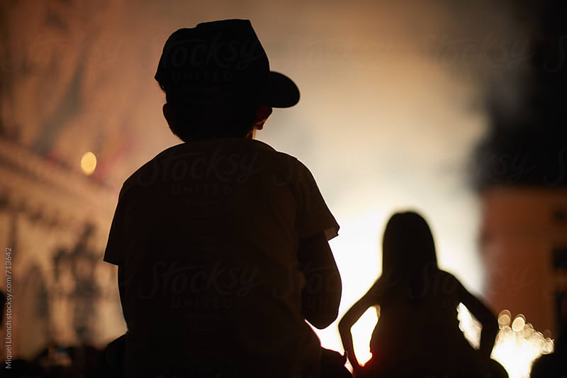 Silhouette of two children in a fire parade by Miquel Llonch for Stocksy United