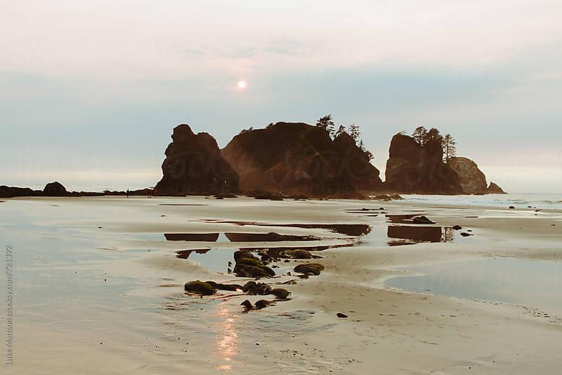 The Sun Sets Over Rock Formations On The Shore Along The Washington Coast by Luke Mattson for Stocksy United