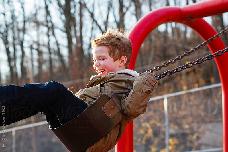 Happy Child on Swing in the City by Holly Clark for Stocksy United