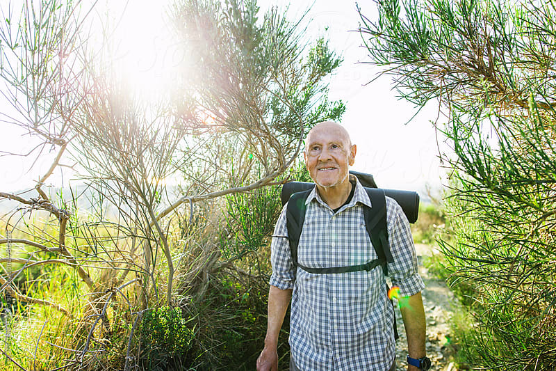 Senior man hiking in the woods on sunny day. by BONNINSTUDIO for Stocksy United