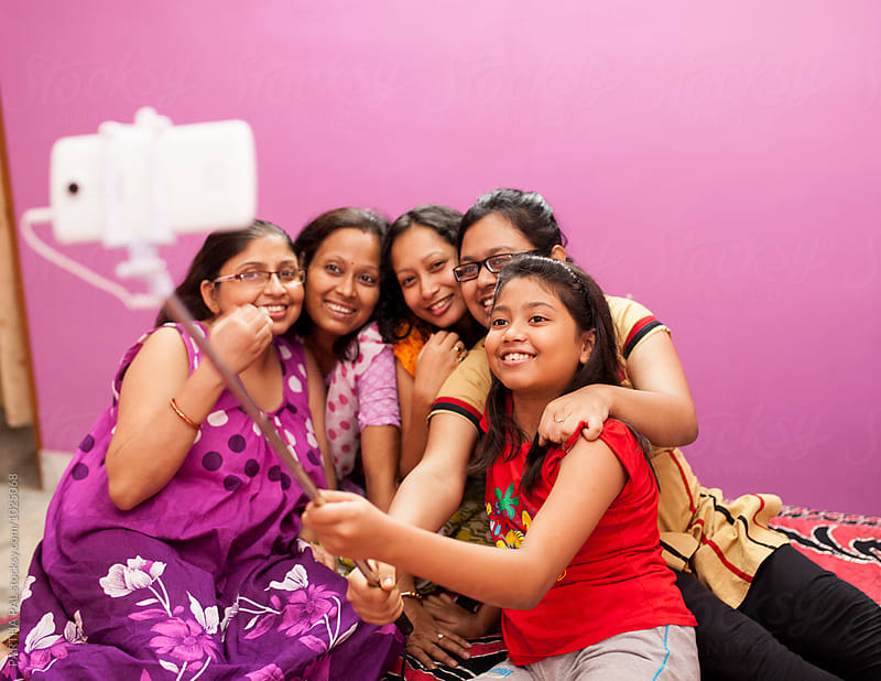 Girls and women sooting selfie with selfie stand by PARTHA PAL for Stocksy United