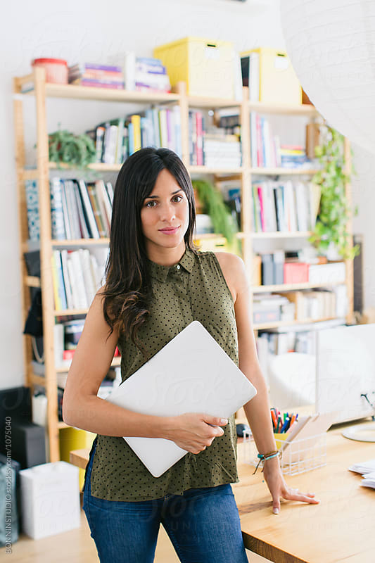 Portrait of a brunette businesswoman standing in a beautiful office.  by BONNINSTUDIO for Stocksy United