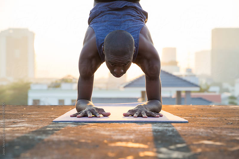 Closeup of a handsome young man doing a hand stand during an intense yoga practice  by Jovo Jovanovic for Stocksy United