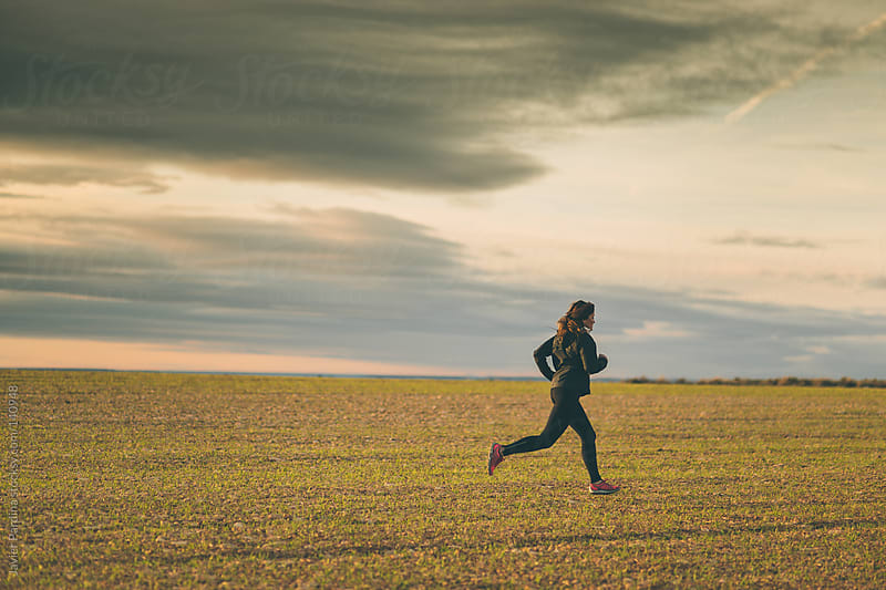 young woman running in the fields at sunset by Javier Pardina for Stocksy United