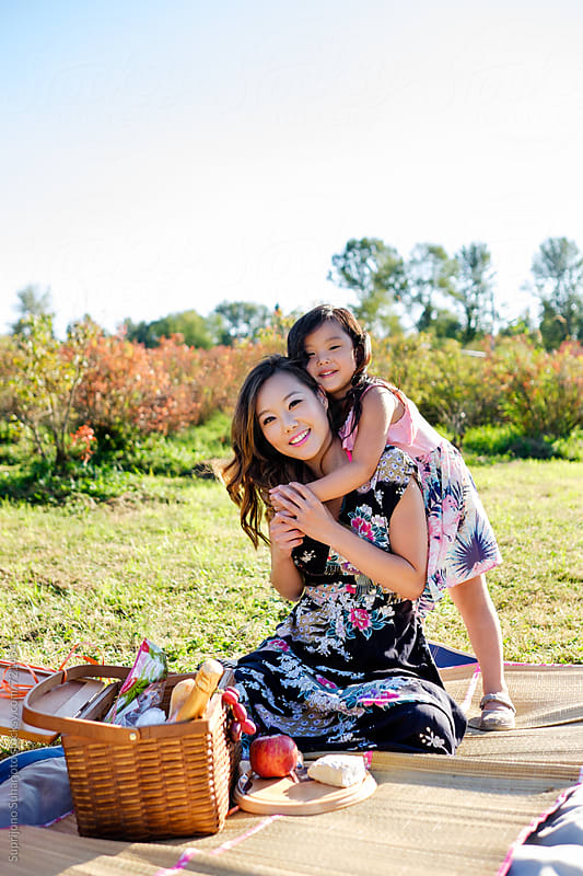 Happy Asian mother and daughter having a picnic in a park by Suprijono Suharjoto for Stocksy United
