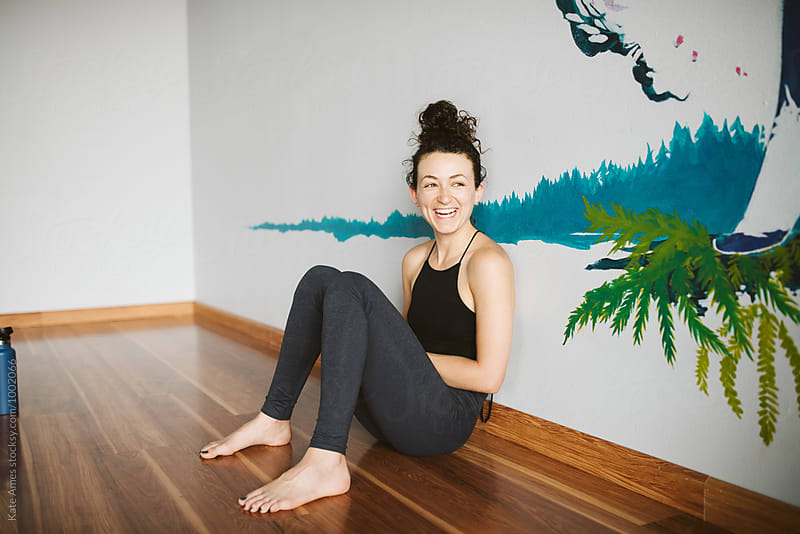 Beautiful young woman hanging out in yoga studio. by Kate Daigneault for Stocksy United