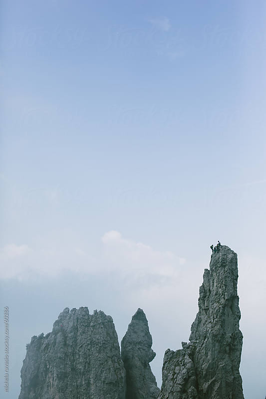 A group of climbers on the top of a rock by michela ravasio for Stocksy United