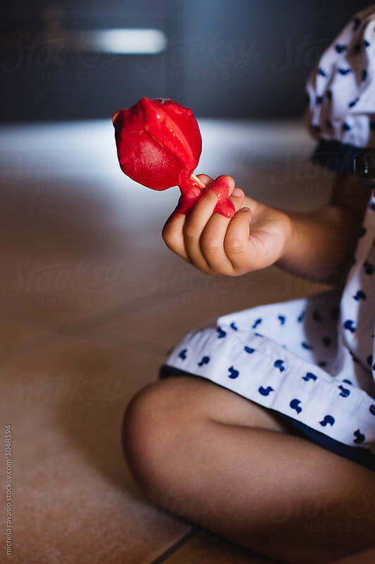 Strawberry ice cream melted in the hands of a little girl by michela ravasio for Stocksy United