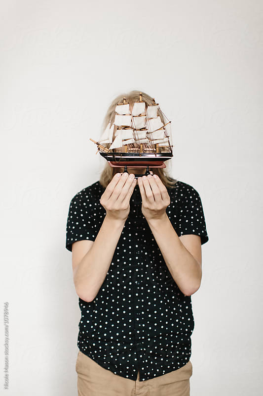 man holding model ship in front of face against white wall by Nicole Mason for Stocksy United