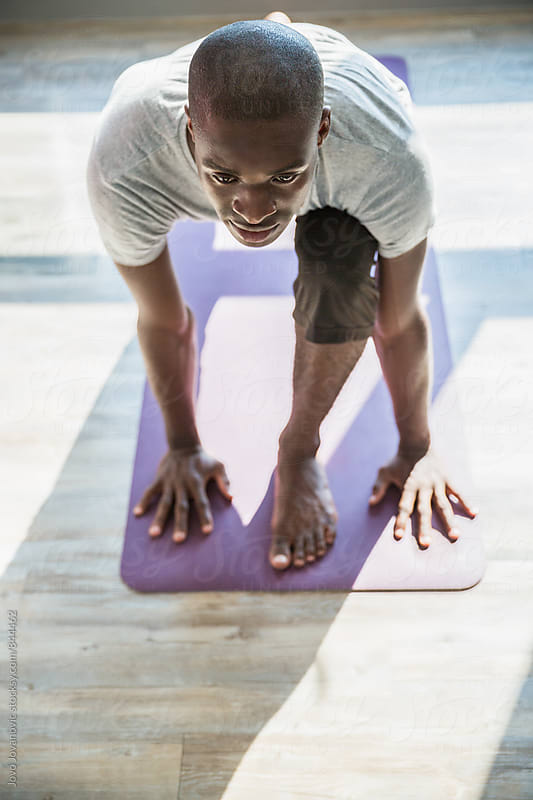 Vertical view of a dark skin man in a yoga practice on a purple yoga mat  by Jovo Jovanovic for Stocksy United