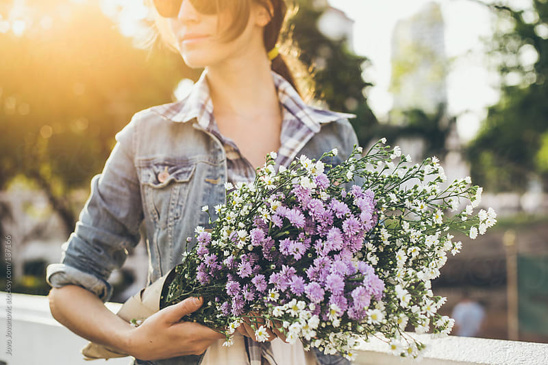 Beautiful girl holding a bouquet of wildflowers on a sunny day. by Jovo Jovanovic for Stocksy United