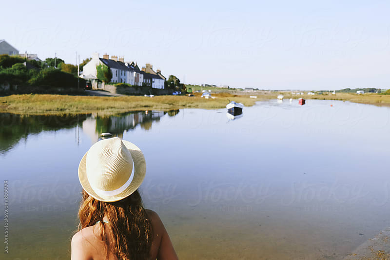 Young woman looking at boats in a estuary by Léa Jones for Stocksy United