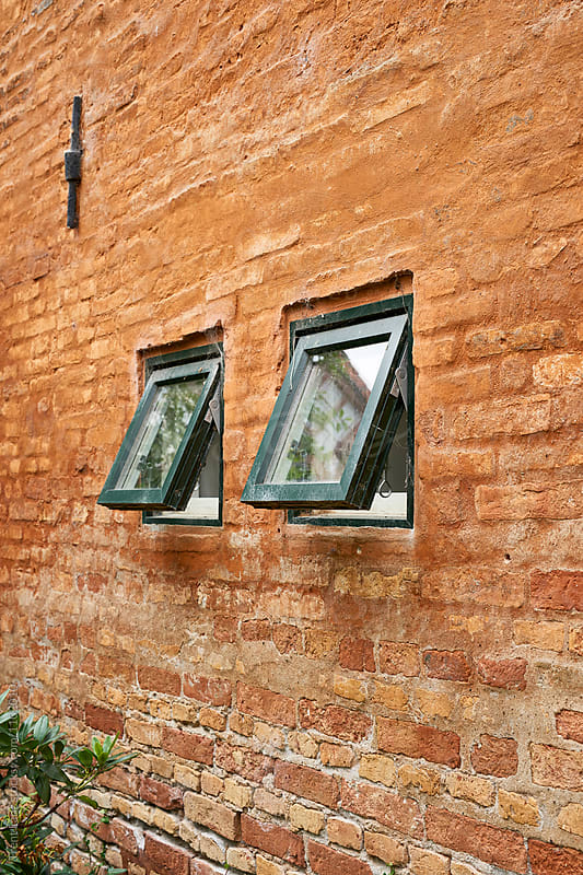 Two open windows in brickwall by Trent Lanz for Stocksy United