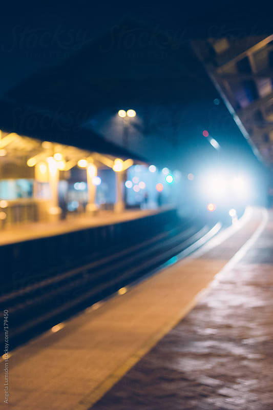 Outdoor train station at night by Angela Lumsden for Stocksy United