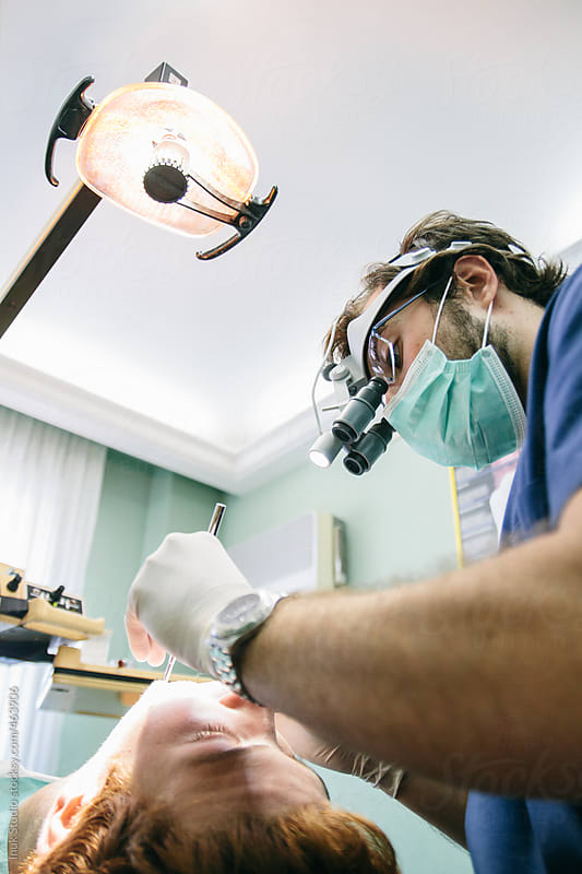 Dentist with microscope glasses during a root canal intervention by Inuk Studio for Stocksy United