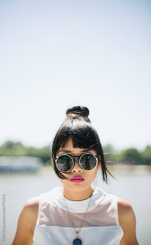 Stylish Asian young woman in white clothes and round sunglasses by Nabi Tang for Stocksy United