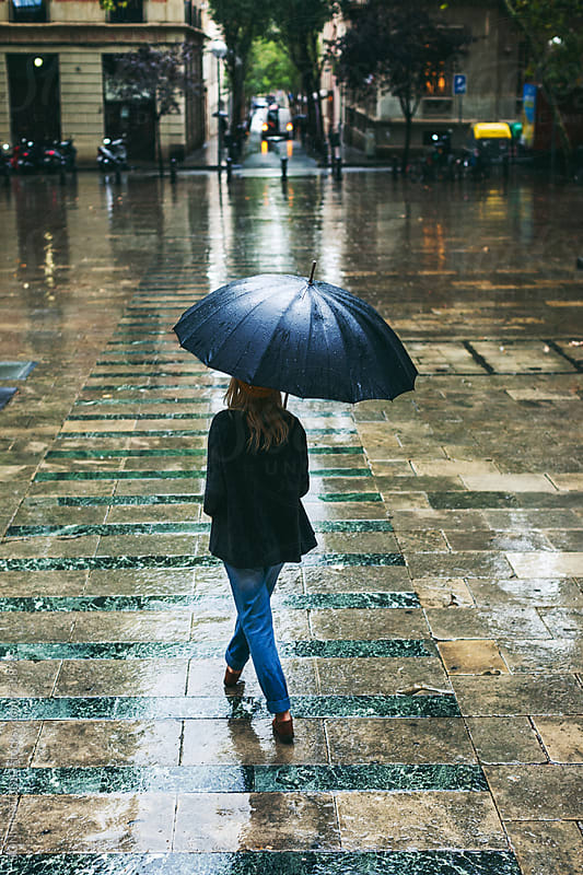 Back view of a woman walking on the street in a rainy day. by BONNINSTUDIO for Stocksy United
