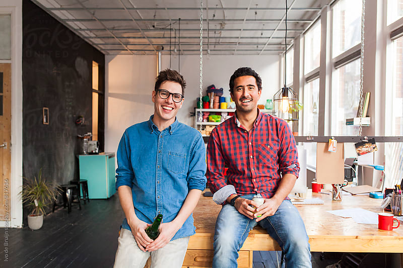 A team of two entrepreneurs or professionals sitting on their desk and having a beer by Ivo de Bruijn for Stocksy United