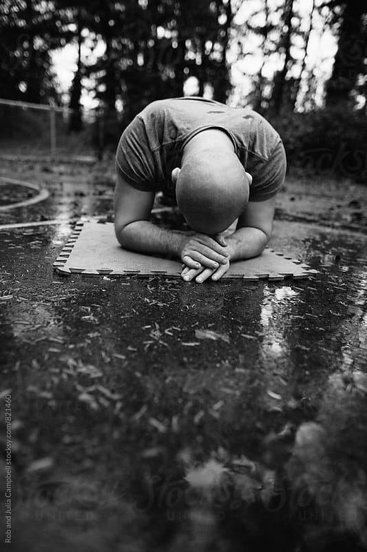 Man holding plank outside on wet ground by Rob and Julia Campbell for Stocksy United