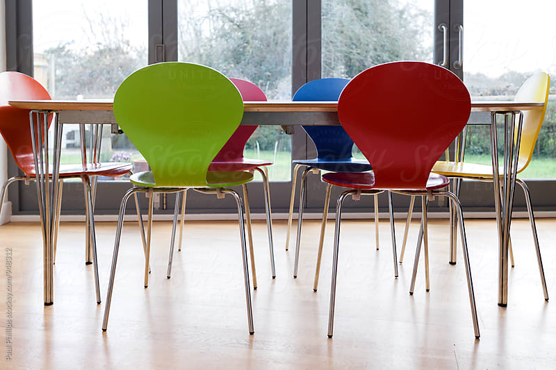 Modern colourful dining chairs around a table. by Paul Phillips for Stocksy United