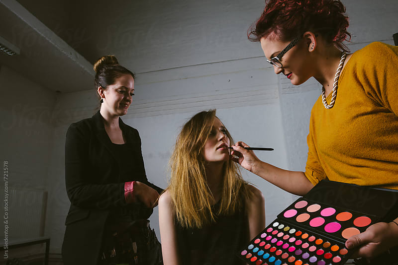 Makeup Artists prepairing female fashion model for photo shooting by Urs Siedentop & Co for Stocksy United