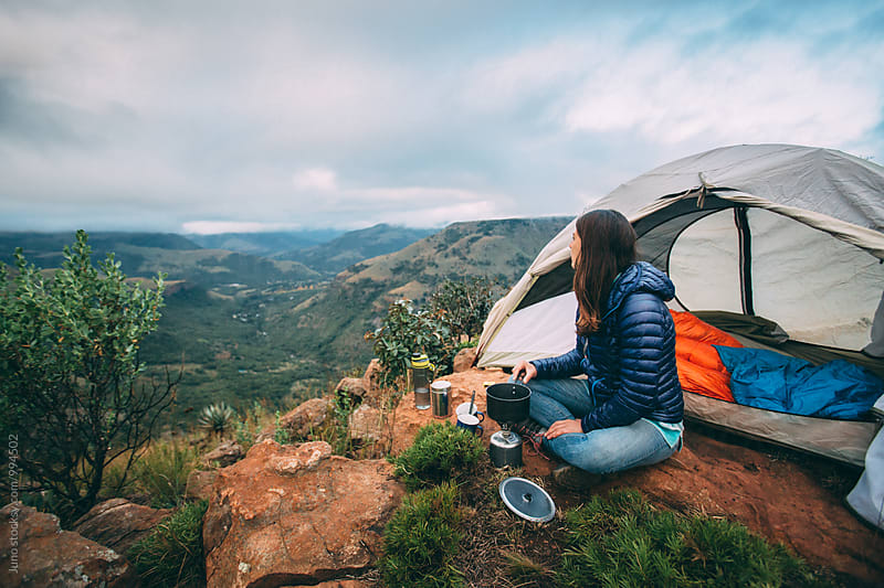 Hiker outside her camp tent cooking on a gas stove by Micky Wiswedel for Stocksy United