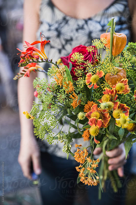 Closeup of a woman holding a large bouquet of flowers by Lior + Lone for Stocksy United