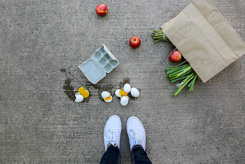 Person standing above fallen groceries and broken eggs by Carolyn Lagattuta for Stocksy United
