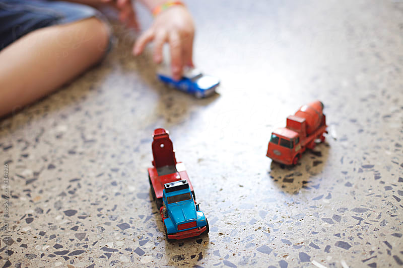 A young boy plays with toy cars and trucks by Natalie JEFFCOTT for Stocksy United