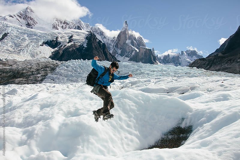Young man jumping a gap on ice on glacier Torre in Patagonia, Argentina by Alejandro Moreno de Carlos for Stocksy United