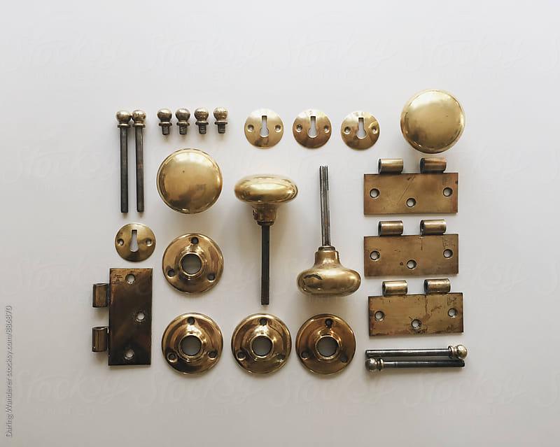 Vintage brass doorknobs and hinge hardware taken apart  by Daring Wanderer for Stocksy United