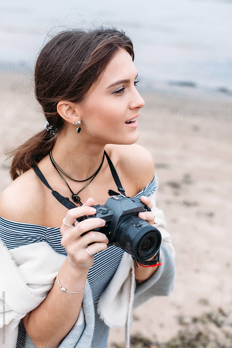 Young stylish beautiful and sensual brunette woman photographer are making pictures on the beach near the