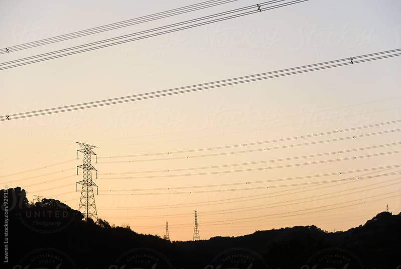 Electricity pylons silhouetted against a sunset by Lawren Lu for Stocksy United