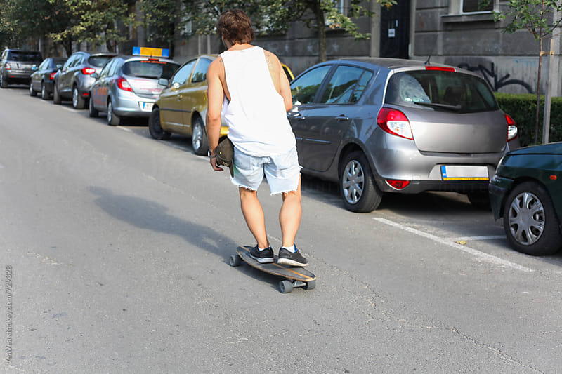Man riding a longboard in the street.  by Marija Mandic for Stocksy United